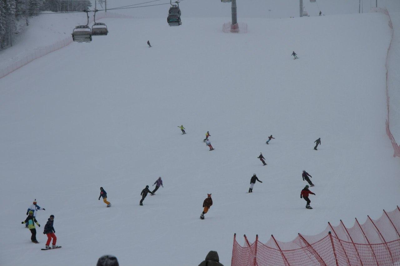 лыжники и сноубордисты спускаются с горы